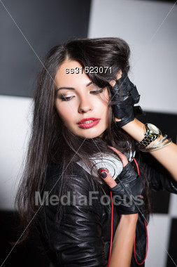 Portrait Of Sexy Brunette Posing With Headphones In The Studio Stock Photo
