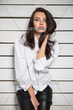 Portrait Of Sexy Brunette Posing In White Shirt And Black Leather Pants Stock Photo