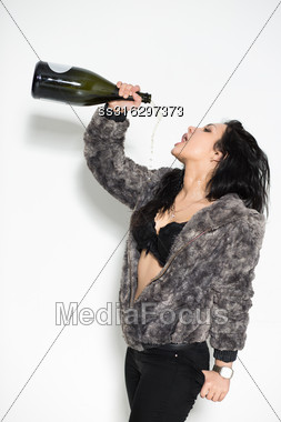 Portrait Of Sexy Brunette Pouring Herself From A Big Bottle Stock Photo