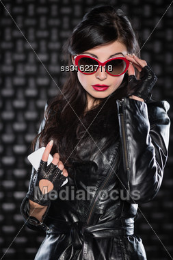 Portrait Of Sexy Brunette Wearing Black Jacket And Red Sunglasses Stock Photo