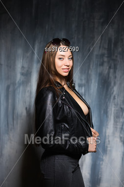 Portrait Of Sexy Smiling Brunette Posing In Black Jacket And Jeans Stock Photo