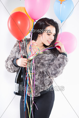 Portrait Of Smiling Brunette With A Big Bottle And Balloons Wearing Furry Jacket Stock Photo