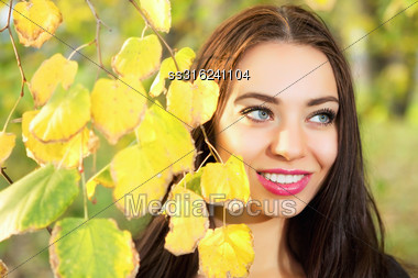 Portrait Of Smiling Brunette Posing Behind Yellow Leaves Stock Photo