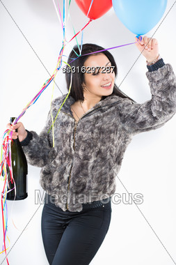 Portrait Of Smiling Woman With A Big Bottle And Balloons Wearing Furry Jacket Stock Photo