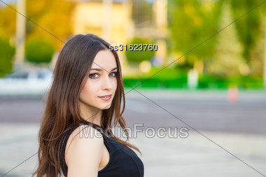 Portrait Of Smiling Young Brunette Posing Outdoors Stock Photo