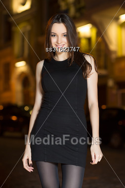 Portrait Of Smiling Young Woman Posing In The Evening Stock Photo