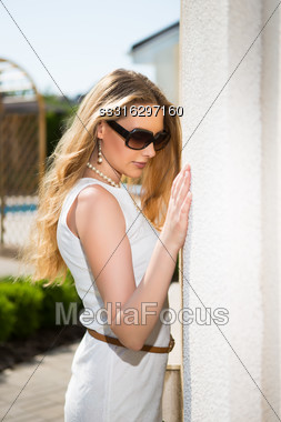 Portrait Of Thoughtful Blond Woman Wearing White Dress And Sunglasses Posing Outdoors Stock Photo