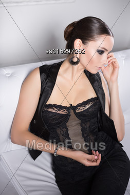 Portrait Of Thoughtful Brunette In Black Lingerie And Vest Posing On White Sofa Stock Photo