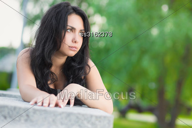 Portrait Of Thoughtful Brunette Posing Near The Stone Fence Stock Photo