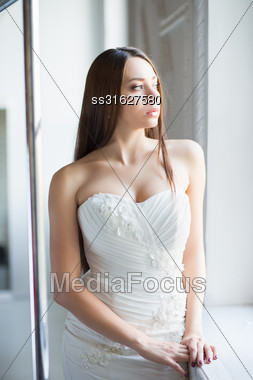 Portrait Of Thoughtful Brunette Posing In Wedding Dress Stock Photo