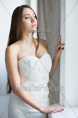 Portrait Of Thoughtful Brunette Wearing Wedding Dress Stock Photo