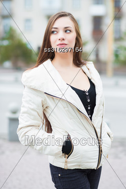 Portrait Of Thoughtful Brunette Wearing White Jacket Posing Outdoors Stock Photo