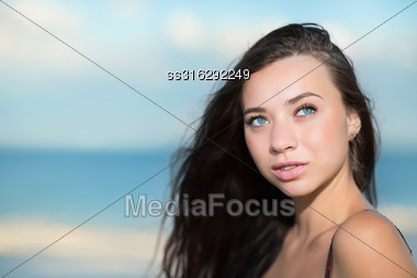Portrait Of Thoughtful Young Brunette On The Beach Stock Photo
