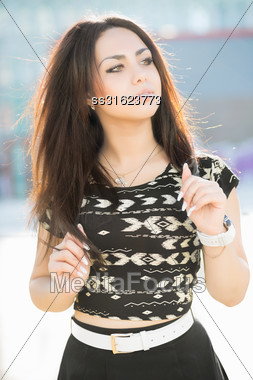 Portrait Of Thoughtful Young Brunette Posing Outdoors Stock Photo