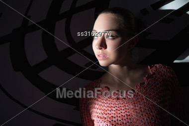 Portrait Of Thoughtful Young Lady Wearing Knitted Sweater Posing Near Wall Stock Photo