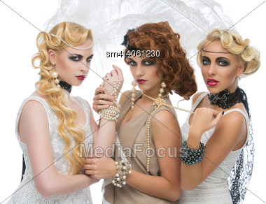 Portrait Of Three Beautiful Girls Wearing Retro Styled Dresses And Accessories Over White Background Stock Photo
