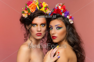 Portrait Of Two Young Beautiful Brunette Girls Wearing Flower Headbands Over Red Background Stock Photo