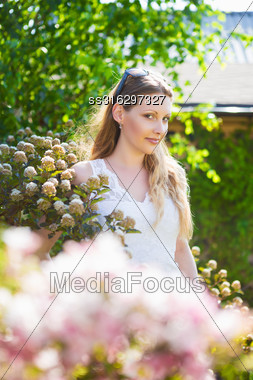 Portrait Of Young Beautiful Blond Woman Posing In Bushes Stock Photo