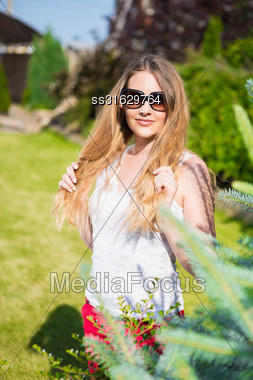 Portrait Of Young Beautiful Blond Woman In Sunglasses Posing Outdoors Stock Photo