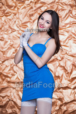 Portrait Of Young Beautiful Brunette Posing In Blue Dress And White Gloves Stock Photo