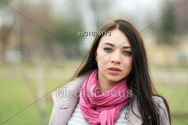 Portrait Of Young Brunette With Pink Scarf Posing Outside Stock Photo