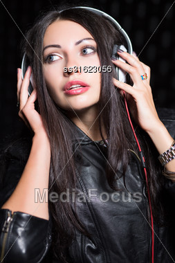 Portrait Of Young Brunette Posing With Headphones. Isolated On Black Stock Photo