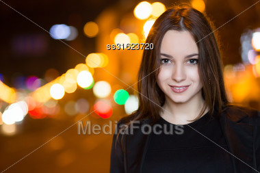 Portrait Of Young Brunette Posing Outdoors In The Evening Stock Photo