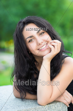 Portrait Of Young Cheerful Brunette Posing Near Stone Fence Stock Photo