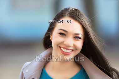 Portrait Of Young Cheerful Brunette Posing Outdoors Stock Photo