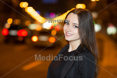 Portrait Of Young Cheerful Woman Posing Outdoors In The Evening Stock Photo