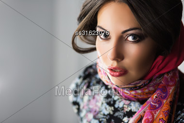 Portrait Of Young Excited Brunette In Flowered Dress And Scarf Stock Photo