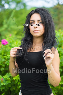 Portrait Of Young Sexy Woman Posing Near The Bushes Stock Photo