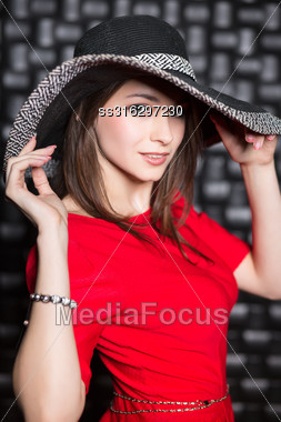 Portrait Of Young Woman Posing In Red Dress And Hat Stock Photo