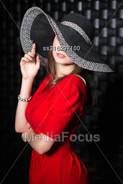 Portrait Of Young Woman Wearing Red Dress And Hat Stock Photo