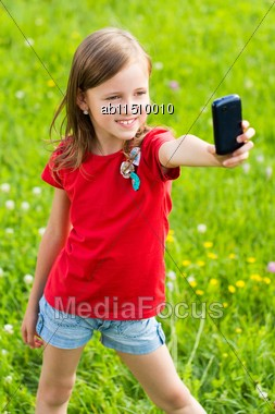 Poser Little Girl Taking Selfie With Her Smartphone Stock Photo