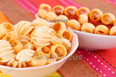 Potato Chips And Red Sauce Isolated On Colorful Tablecloth Stock Photo