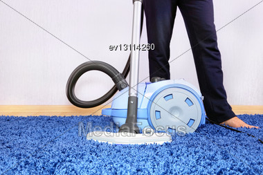 Powelful Vacuum Cleaner In Action-a Men Cleaner A Carpet Stock Photo