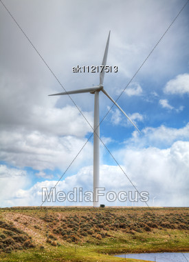 Power Mills Field Against Cloudy Sky Stock Photo