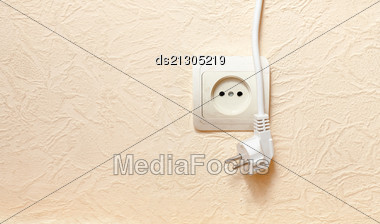Power Outlet With Plugged In Cord Closeup On Beige. Limited Dof Focus On Outlet Stock Photo