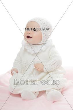 Prankish Baby Girl Wearing White Clothes. High Key Stock Photo