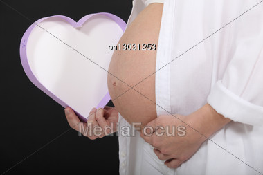 Pregnant Woman Holding A Heart Shaped Box Stock Photo