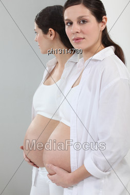 Pregnant Woman Standing In Front Of A Mirror Stock Photo