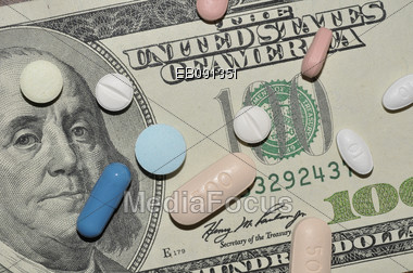 Prescription medication laying on a $100 bill Stock Photo