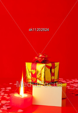Presents And Burning Heart Shaped Candle With Blank Card Stock Photo