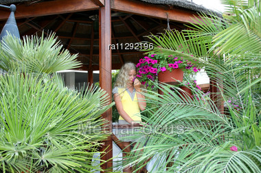 Pretty Blond Girl Between Palms With Pink Flowers Stock Photo