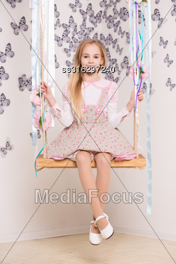 Pretty Blond Girl Posing On The Swing Stock Photo