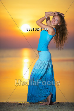 Pretty Blond Woman In Blue T-shirt And Skirt Posing At The Sunset Stock Photo