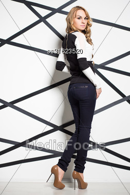 Pretty Blond Woman In Jeans And Blouse Posing Near The Wall Stock Photo