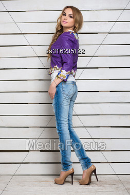 Pretty Blond Woman In Jeans And Purple Jacket Posing Near The White Wooden Wall Stock Photo