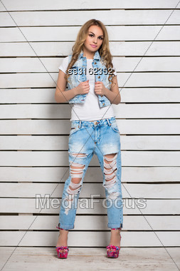 Pretty Blond Woman Posing In Blue Jeans Near White Wooden Wall Stock Photo